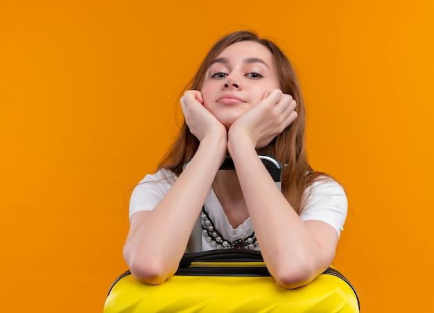 Уверенная молодая девушка-путешественница кладет руки на чемодан на изолированном оранжевом пространстве с копией пространства