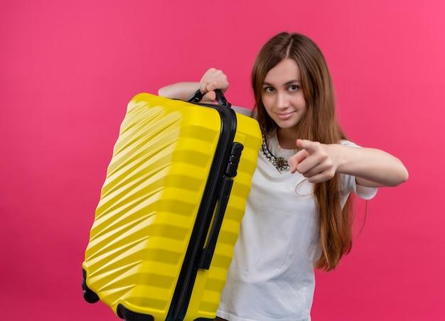 Уверенная молодая девушка-путешественница поднимает чемодан и указывает на изолированное розовое пространство