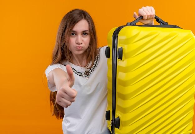 Уверенная молодая девушка-путешественница поднимает чемодан и показывает палец вверх на изолированном оранжевом пространстве