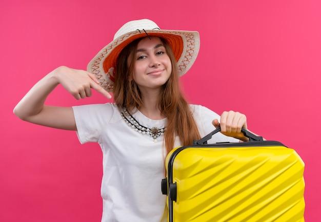 Fiducioso giovane viaggiatore ragazza che indossa il cappello tenendo la valigia e indicandolo su uno spazio rosa isolato