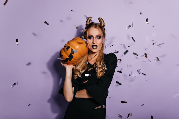 Confident young witch holding halloween pumpkin.  photo of pretty vampire girl standing on purple wall.