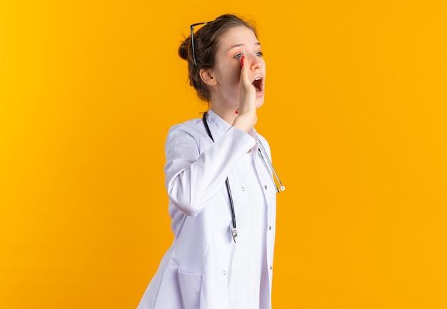Fiduciosa giovane donna in uniforme da medico con stetoscopio che tiene la mano vicino alla bocca chiamando qualcuno che guarda di lato