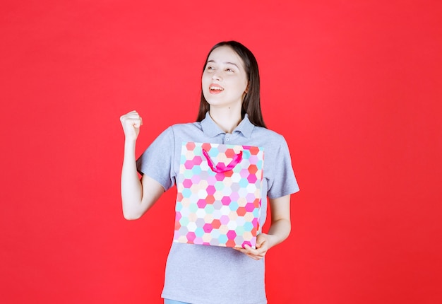 Confident young woman holding colorful shopping bag and squeeze her fist