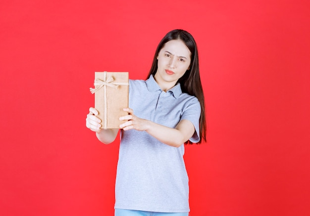 Confident young woman holding gift box