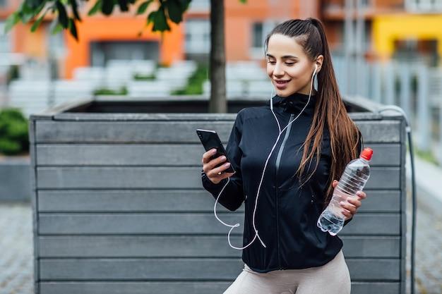 아침 달리기 후 신선한 공기를 마시며 물과 헤드폰을 착용한 자신감 넘치는 젊은 여성. 건강한 개념입니다.