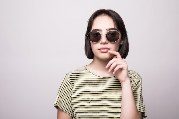 Уверенная молодая женщина, глядя через изолированные солнцезащитные очки
