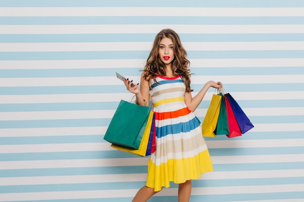 Confident young woman posing with phone and purchases. indoor shot of curious long-haired girl holding bags from boutique.