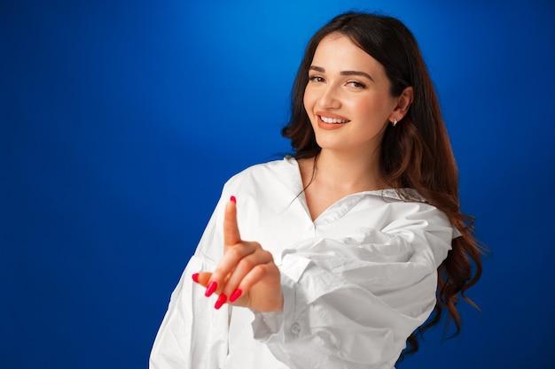 Уверенно молодая женщина показывает жест стоп, указывая пальцем