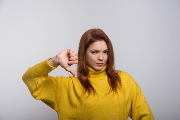 親指を下に見せて自信を持って若い女性