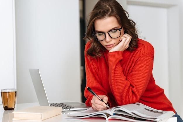 Уверенно молодая женщина сидит за кухонным столом дома, учится с портативным компьютером и рабочей тетрадью