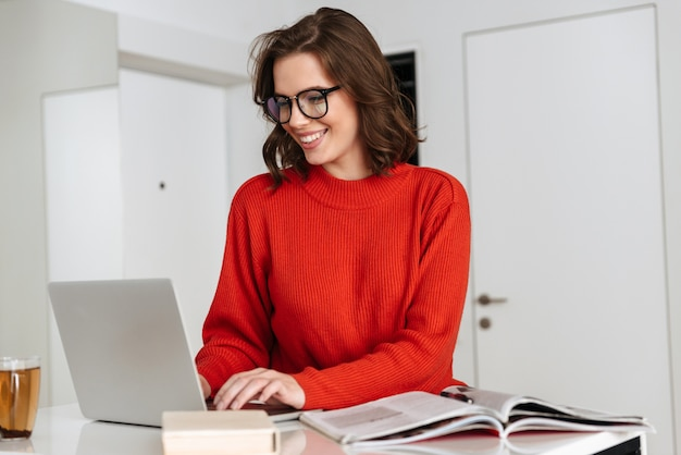 Confident young woman sitting at the kitchen table at home, studying with laptop computer and workbook