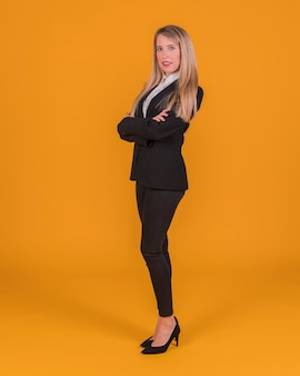Confident young woman standing against an orange backdrop