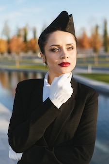 Confident young woman stewardess in uniform waiting for her flight in the park