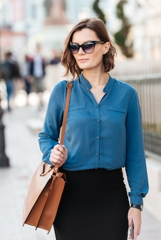 Confident young woman in sunglasses on street