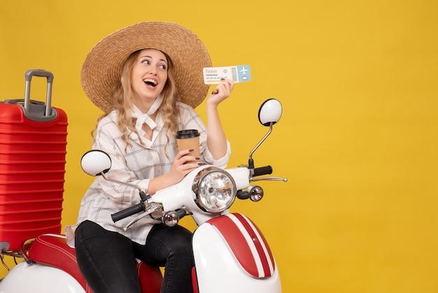 모자를 쓰고 오토바이에 앉아 노란색에 커피와 티켓을 들고 자신감을 젊은 여성
