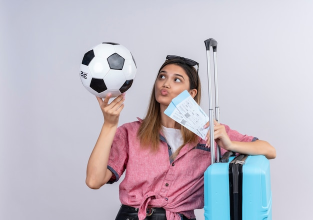 A confident young woman wearing red shirt and sunglasses looking at soccer ball while holding plane tickets and blue suitcase on a white wall