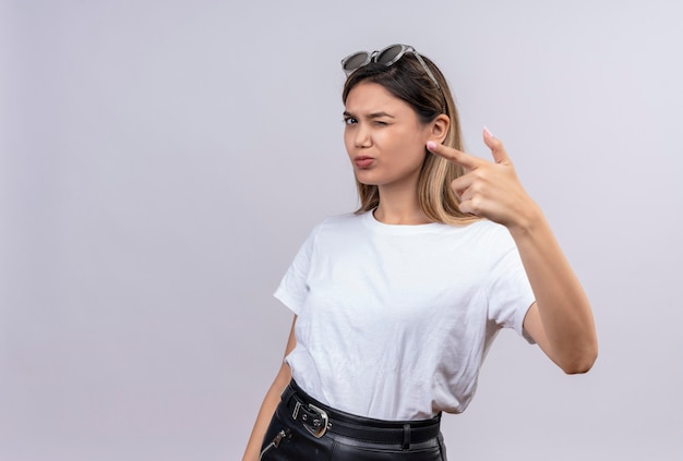 A confident young woman in white t-shirt wearing sunglasses on her head pointing at something with index finger while looking on a white wall