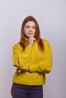 Confident young woman with finger on chin