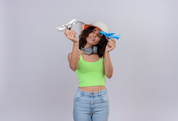 A confident young woman with short hair in green crop top in headphones wearing sun hat holding blue and white toy airplanes in hands on a white background