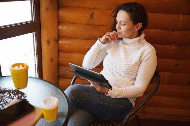 木製の壁を背景にカフェに座ってタブレットに取り組んでいる自信を持って若い女性。オンラインビジネスまたは研究の概念