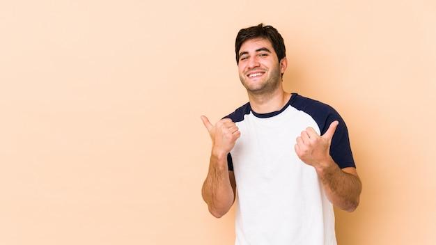 Молодой человек изолированный на бежевом поднимая оба больших пальца руки вверх, усмехаться и confidont.