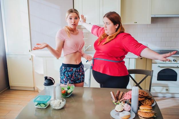 自信を持って構築された若い女性はカメラを見て不幸です。プラスサイズモデルのウエストを測っています。太りすぎの女性は真剣に彼女の友人を見てください。腰周りはやわらかなブルーのテープ。