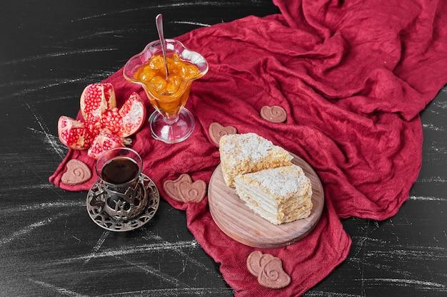 Конфитюр и кусочки торта на красном полотенце с чаем.