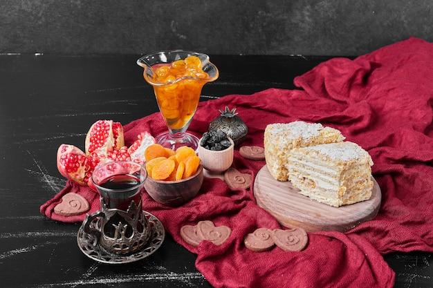 お茶と赤いタオルの上にコンフィチュールとケーキのスライス。