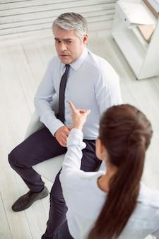 직장에서의 갈등. 좋은 불행한 무서워 남자가 의자에 앉아 그녀와 충돌하면서 동료를보고