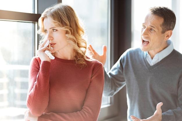 家族の対立。彼の妻の後ろに立って、彼の感情を表現しながら彼女に叫んでいる怒っている感情的な男