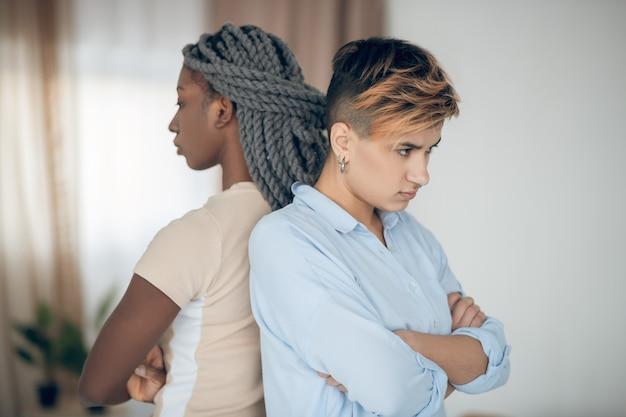 Конфликт. однополая пара ссорится и стоит спиной к спине