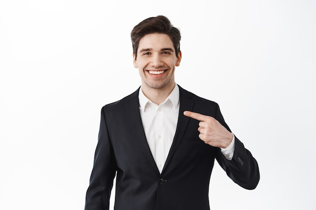 Confreal estate agent points at himself with pleased, determined smile, self-promoting, choose me gesture, stands against white wall