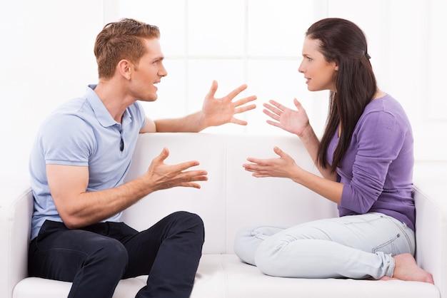 대립하는 커플. 화난 젊은 남자와 여자는 소파에 앉아 서로 소리를 지르며 몸짓을 한다