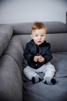 Confused adorable little blond boy with blue eyes sitting on sofa in living room