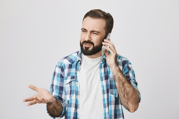 Confused adult bearded guy have phone conversation