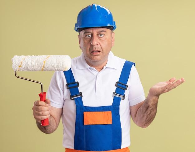 L'uomo adulto confuso del costruttore in uniforme tiene la spazzola del rullo isolata sulla parete verde oliva