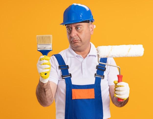 L'uomo adulto confuso del costruttore in guanti protettivi da portare dell'uniforme tiene il pennello e la spazzola del rullo isolati sulla parete arancione