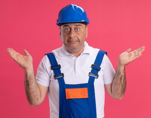 Uomo caucasico adulto confuso del costruttore in uniforme che tiene le mani aperte sul rosa