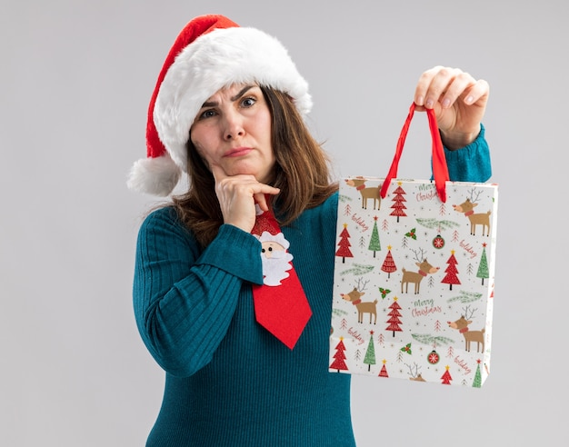 산타 모자와 산타 넥타이와 혼란 성인 백인 여자 턱에 손가락을 넣고 복사 공간이 흰 벽에 고립 된 종이 선물 상자를 보유