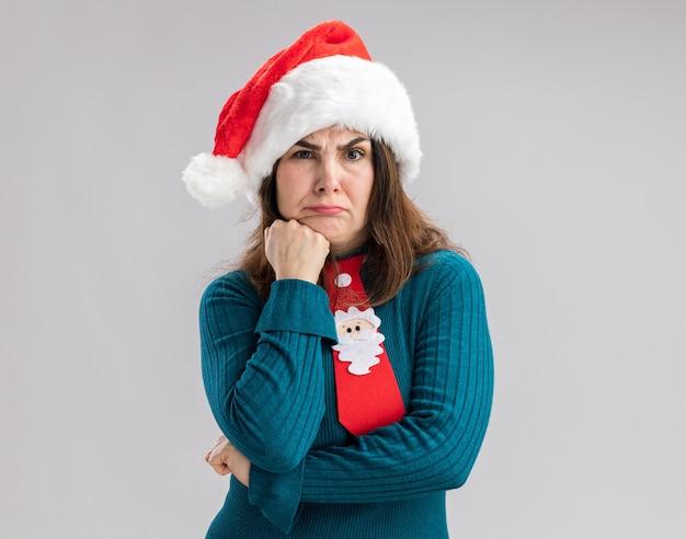 산타 모자와 산타 넥타이와 혼란 성인 백인 여자 복사 공간이 흰 벽에 고립 된 턱에 주먹을 넣습니다