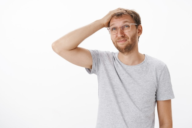 Растерянный взрослый отец с щетиной в очках почесывает макушку ухмыляется и прищуривается, смотрит вдалеке невежественный и сомневаемый, встревоженный, стоит над серой стеной