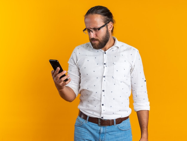 Bell'uomo adulto confuso con gli occhiali che tiene e guarda il telefono cellulare isolato sul muro arancione