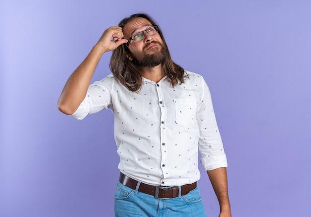 Uomo bello adulto confuso con gli occhiali che tiene la mano sulla testa guardando in alto isolato sul muro viola con spazio copia