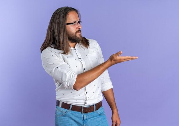 Uomo bello adulto confuso con gli occhiali guardando il lato che mostra la mano vuota isolata sul muro viola