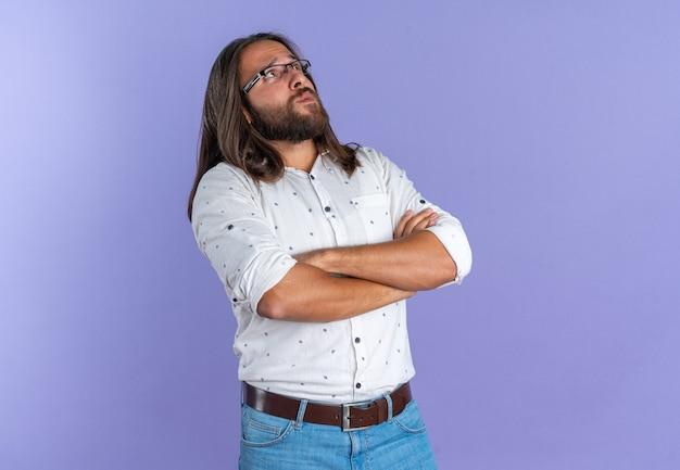 Uomo bello adulto confuso che indossa occhiali in piedi con postura chiusa guardando in alto isolato sul muro viola con spazio copia