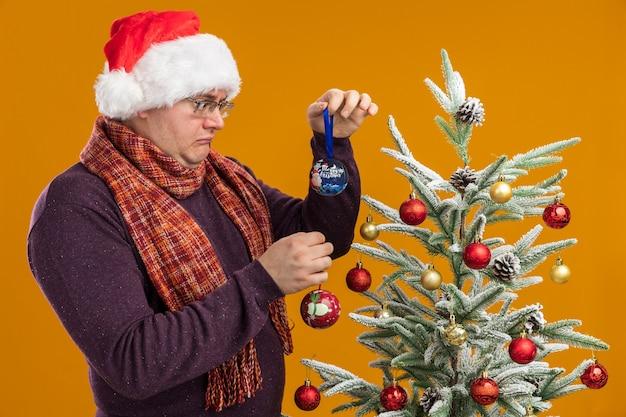 オレンジ色の壁に隔離されたものを見ているクリスマスつまらないものを保持している装飾されたクリスマスツリーの近くの縦断ビューで立っている首の周りにスカーフとメガネとサンタ帽子を身に着けている混乱した大人の男