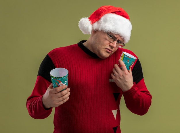 Confused adult man wearing glasses and santa hat holding christmas coffee cups tilting head to side looking at camera isolated on olive green background