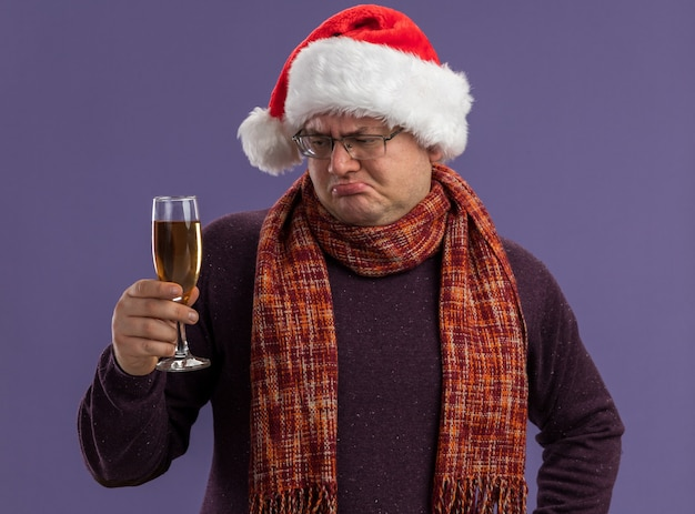 Confused adult man wearing glasses and santa hat with scarf around neck holding and looking at glass of champagne isolated on purple background