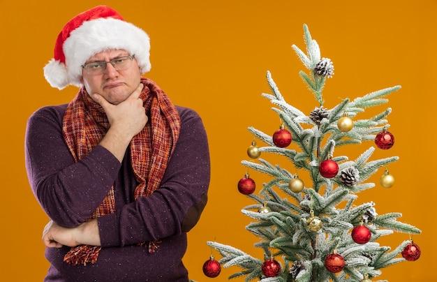 Uomo adulto confuso che indossa occhiali e cappello da babbo natale con sciarpa intorno al collo in piedi vicino all'albero di natale decorato tenendo la mano sul mento isolato sul muro arancione