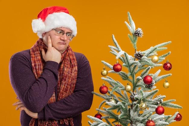 Uomo adulto confuso che indossa occhiali e cappello da babbo natale con sciarpa intorno al collo in piedi vicino all'albero di natale decorato che guarda in basso tenendo la mano sul mento isolato sul muro arancione